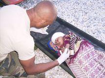 L'Adjudant Fontaine prodiguant des soins à une petite Afghane